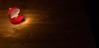 Обручальное кольцо в коробке красного цвета стоит на темной таблице дерева Стоковое Фото