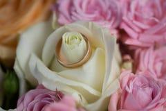 Обручальное кольцо золота на подняло Стоковое Фото