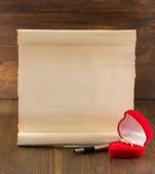 Обручальное кольцо и постаретая бумага на древесине Стоковое Фото