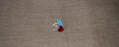 Обручальное кольцо с голубой зажимкой для белья на предпосылке стоковая фотография rf