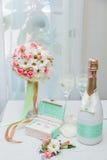 Обручальные кольца, букет невесты около бутылки шампанского и 2 рюмки на белизне Стоковое Фото