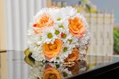 Обручальные кольца лежат на букете оранжевых роз и белых цветов Стоковое Фото