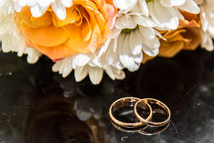 Обручальные кольца лежат на букете оранжевых роз и белых цветов Стоковое Изображение RF