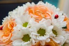 Обручальные кольца лежат на букете оранжевых роз и белых цветов Ladybug Стоковое Изображение