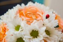 Обручальные кольца лежат на букете оранжевых роз и белых цветов Ladybug Стоковые Изображения RF