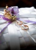 обручальные кольца лежа на украшенном валике сатинировки Стоковые Изображения