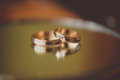 Обручальные кольца жениха и невеста на зеркале Стоковые Изображения RF