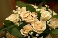 Обручальные кольца золота лежат на букете роз Стоковое Изображение