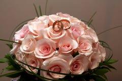 Обручальные кольца золота лежат на букете роз Стоковая Фотография