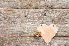 Обручальные кольца золота и бумажное сердце Стоковая Фотография