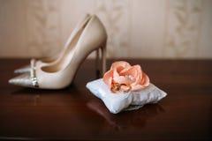 Обручальные кольца золота на белизне украшают подушку, ботинки невесты белые на предпосылке Стоковые Фото