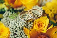 Обручальные кольца золота на желтом букете невесты Объявление lo Стоковые Фото