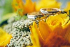 Обручальные кольца золота на желтом букете невесты Объявление lo Стоковое фото RF