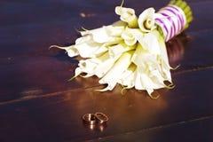 Обручальные кольца и букет белых лилий Стоковые Изображения
