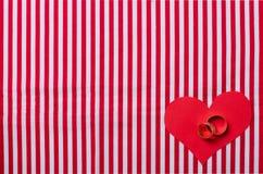 Обручальные кольца и бумажное сердце Стоковые Фотографии RF