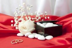Обручальные кольца и благосклонности на шикарной ткани Стоковая Фотография