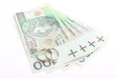 Обручальные кольца и деньги на белой предпосылке Стоковое Изображение