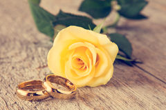 Обручальные кольца и роза желтого цвета Стоковые Изображения