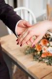 Обручальные кольца и руки жениха и невеста молодые пары свадьбы на церемонии супружество Человек и женщина в влюбленности 2 счаст Стоковая Фотография