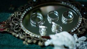 Обручальные кольца и серьги лежа на зеркале Стоковые Изображения RF