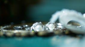 Обручальные кольца и серьги лежа на зеркале Стоковые Фото
