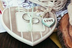 Обручальные кольца и сердце с влюбленностью подписывают на церемонии Стоковая Фотография RF