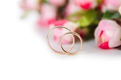 Обручальные кольца и цветки изолированные на белой предпосылке Стоковое фото RF
