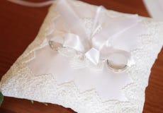 Обручальные кольца на вышитой подушке Стоковые Фото