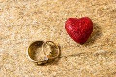 Обручальные кольца на естественном камне с включениями родного золота Руки и сердца предложения Стоковое Фото