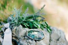 Обручальные кольца на камне и оливковой ветке Ювелирные изделия свадьбы Стоковая Фотография RF