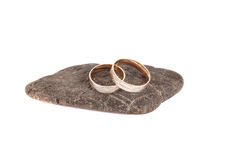 Обручальные кольца на камне на белой изоляции предпосылки Стоковое Изображение