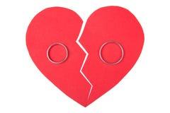 Обручальные кольца на красном разбитом сердце изолированном на белизне Стоковая Фотография RF