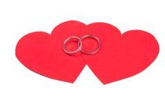 Обручальные кольца на красном сердце изолированном на белизне Стоковое фото RF
