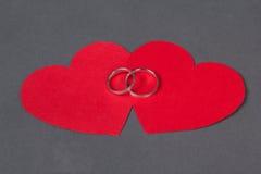 Обручальные кольца на красном сердце над серым цветом Стоковые Фото