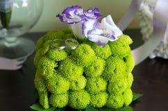 Обручальные кольца на кубе зеленых хризантем Стоковое Изображение RF