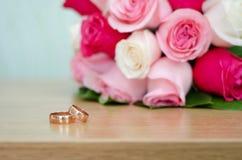 Обручальные кольца на предпосылке букета Стоковая Фотография