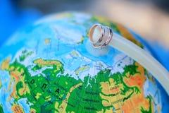 Обручальные кольца на предпосылке глобуса, карты мира Стоковые Фото