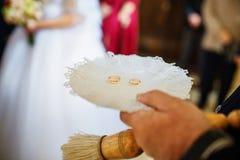 Обручальные кольца на плите под рукой священника на свадебной церемонии на Стоковые Изображения RF