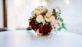 Обручальные кольца на таблице на кафе против букета свадьбы Стоковые Изображения RF