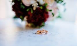 Обручальные кольца на таблице на кафе против букета свадьбы Стоковая Фотография