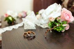 Обручальные кольца на таблице около цветков Стоковое Фото