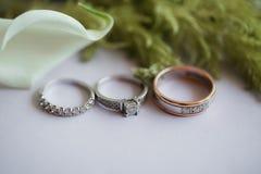 обручальные кольца на таблице с лилиями и зелеными цветами calla Стоковые Изображения RF