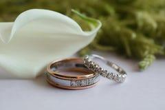 обручальные кольца на таблице с лилиями и зелеными цветами calla Стоковое Изображение