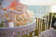 Обручальные кольца на таблице с красивой раковиной Стоковые Фотографии RF