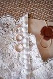 Обручальные кольца от желтого золота лежат на платье невесты Стоковое Изображение