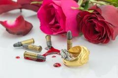 Обручальные кольца приближают к крови и красной розе на белой предпосылке Стоковая Фотография