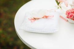 Обручальные кольца прыгают с розовой ложью ленты на белой подушке Стоковые Фото