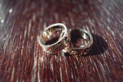 Обручальные кольца с высекать картину на таблице Стоковые Фото
