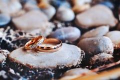 Обручальные кольца с диамантом лежат на камне Стоковая Фотография
