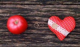 Обручальные кольца, яблоко и сердце на деревянной предпосылке Стоковое Изображение RF